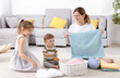 Housewife with children folding freshly washed towels in room