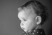 Black And White Image Side View Of A White Toddler Girl Wearing Polka Dot Shirt Looking Away From Camera.