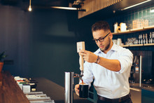Young Businessman Taking Coffee From Coffee Machine