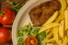 Close Up Of Detailed Grilled Beef Steak With French Fried Potato, Tomato, Served In White Plate On Cutting Board On Wooden Table Background