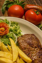 Close Up Of Detailed Well Done Grilled New York Steak With French Fried Potatoes, Tomatoes, Sausage. Served In White Plate On Cutting Board On Wooden Table Background