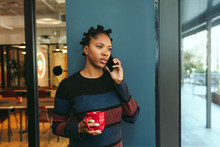 Young Businesswoman Talking On Smartphone While Having Coffee
