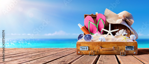 Papiers peints Montagne Beach Accessories In Suitcase On Wooden Pier - Travel Concept