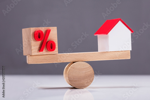 Fototapeta Seesaw Showing Balance Between Percentage Symbol And House Model