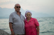 Portrait of elderly caucasian couple by the sea on background mountains