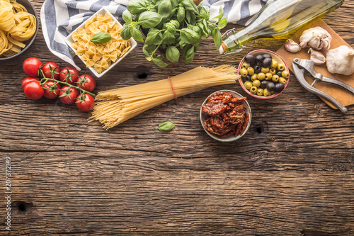 Italian food ingredients pasta olive oil parmesan cheese basil garlic mushrooms tomatoes olives on wooden table