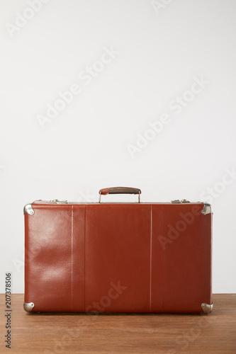 Papiers peints Retro Closed leather suitcase on wooden background
