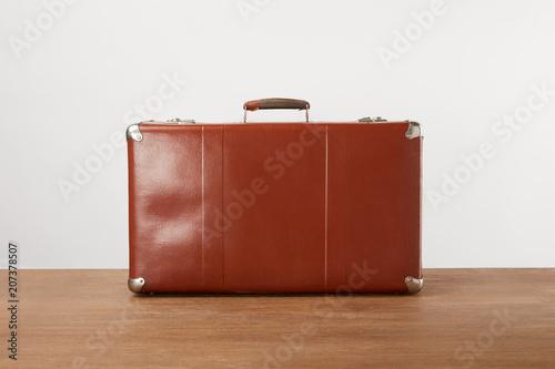 Papiers peints Retro Vintage brown leather suitcase on wooden table