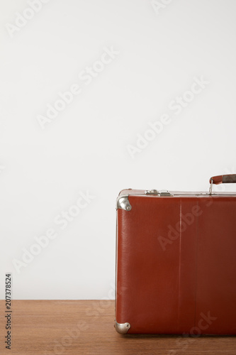 Papiers peints Retro Brown vintage suitcase on wooden table by white wall