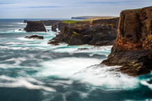The Wild Atlantic Ocean Crashes Against The Sea Stacks, Rocks, And Cliffs Along The Western Shore Of Shetland Islands At Eshaness