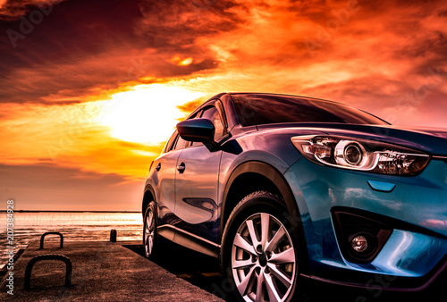 Blue compact SUV car with sport, modern, and luxury design parked on concrete road by the sea at sunset. Front view of beautiful hybrid car. Driving with confidence. Travel on vacation at the beach.