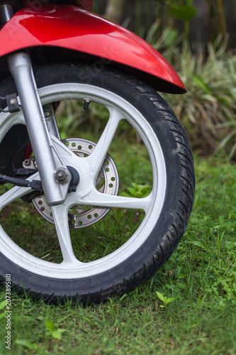 Fragment of front wheel with disc brakes of a red scooter