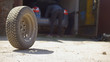 Car wheels rolling on the ground in front of car garage