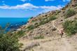 The tourist admires the Sea and Mountains landscape at Cape Meganom, the east coast of the peninsula of Crimea.