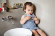 Little girl painting nails in bathroom alone