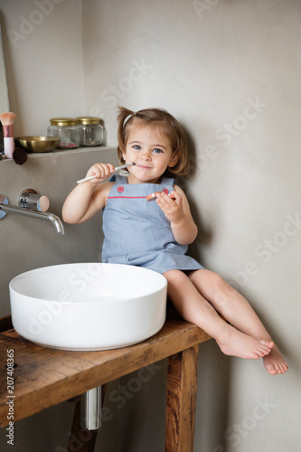 Toddler playing with Mom's makeup in bathroom