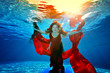 A beautiful woman with a red cloth in her hands with red hair and a red dress dives and floats underwater like a bird in the rays of light on a blue background. Look from below from under the water
