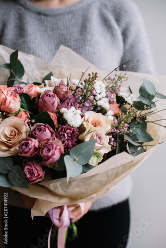 Young florist woman holding freshly made blossoming flower bouquet of roses and eucalyptus on the grey wall background. © anastasianess