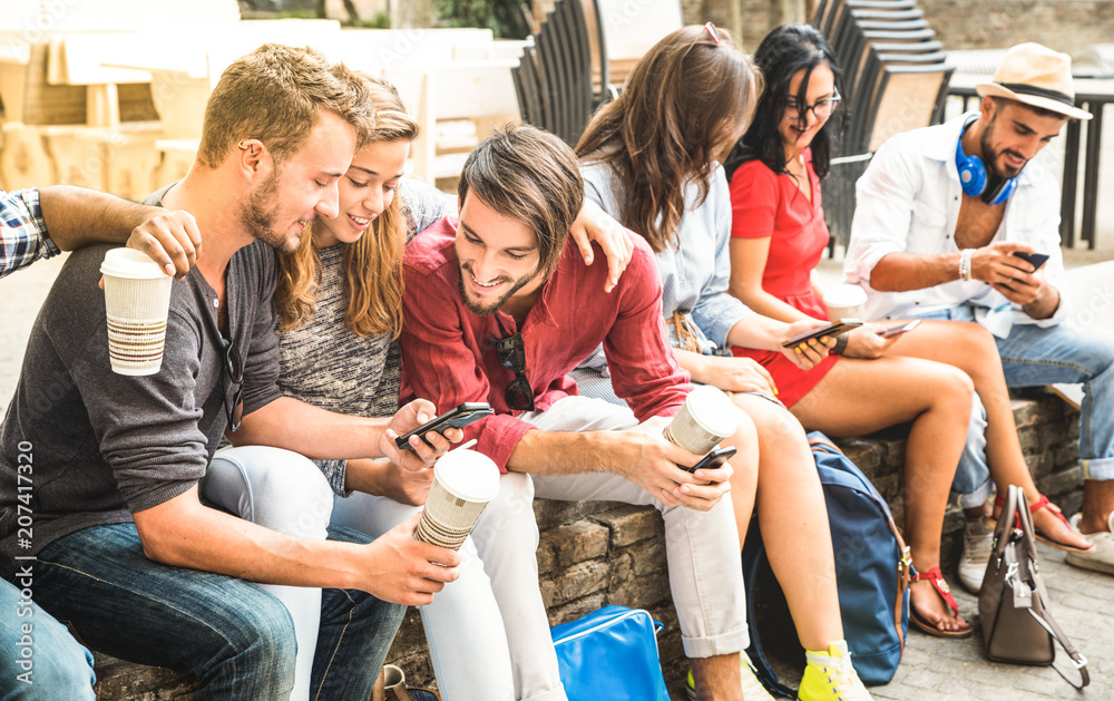 Fototapeta Multiracial millennials group using smart phone at city college backyard - Young people addicted by mobile smartphone - Technology concept with connected trendy friends - Warm vibrance sunshine filter