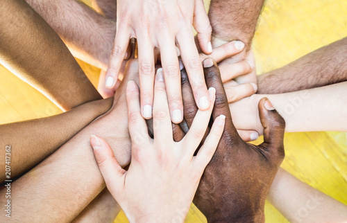 Top view of multiracial stacking hands - International friendship concept with multiethnic people representing peace and unity against racism - Multi racial love and integration between diversity