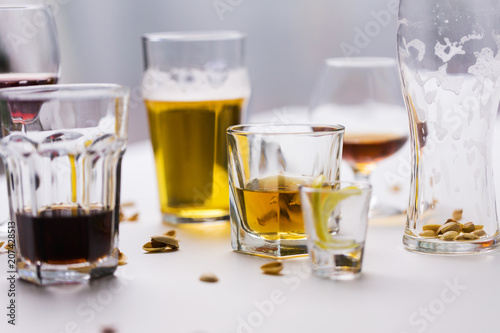 Tuinposter Bar alcohol addiction and drunkenness concept - glasses of different drinks on messy table
