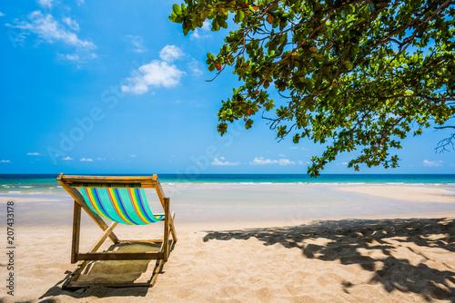 Foto op Plexiglas Indonesië Tropical tree and beach chair at white sand beach and blue sea