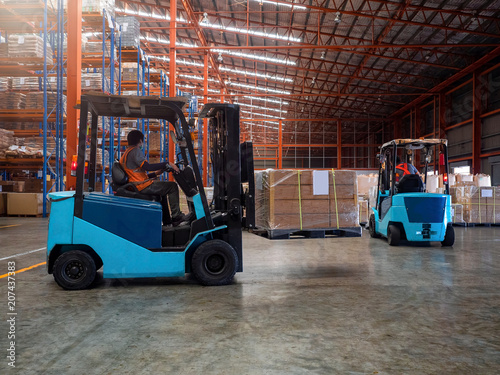 Fotografie, Obraz  Forklift is handling cargo on pallet  in large warehouse.