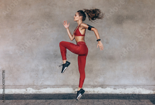 фотографія Sportswoman jumping and stretching