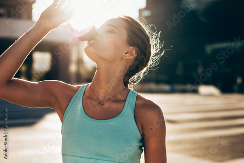 Woman drinking water after workout session