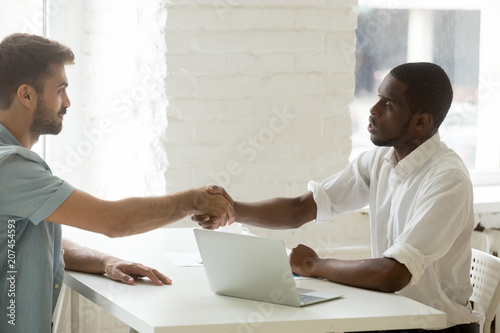 Serious african american boss shaking hand of caucasian job serious african american boss shaking hand of caucasian job candidate thanking for talk greeting m4hsunfo