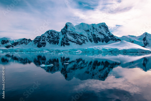 Photo Stands Antarctica Glacier carved snow capped mountains in Antarctica.