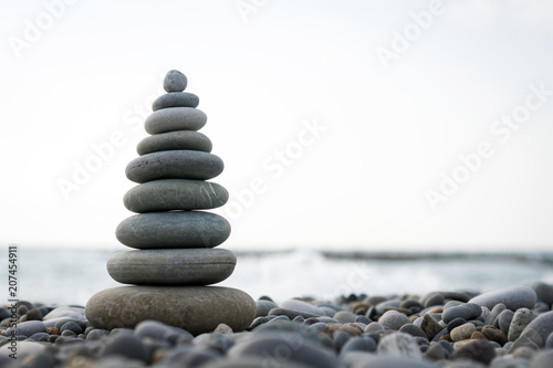 Canvas Prints Zen a pyramid of stones on a pebble beach against the sea and sky.