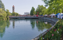 Spokane River In Riverfront Park With Clock Tower Flowers, People, Bridge And Vendors