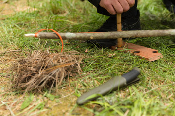 Man using knife and dry materials with friction bow to start a fire in the forest