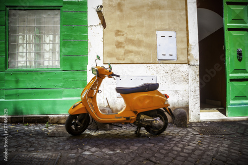 Foto op Canvas Scooter Typical street scene in Rome with a red scooter on an old narrow cobblestoned street. Scooter Vespa parked on old street in Rome, Italy
