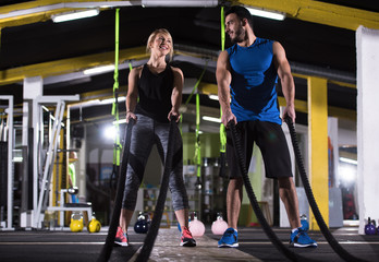 sports couple doing battle ropes cross fitness exercise