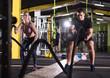 sports couple doing battle ropes cross fitness exercise