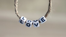 A LOVE Alphabet Hanging On A Rope. An Alphabet Of LOVE One The Soft Background.