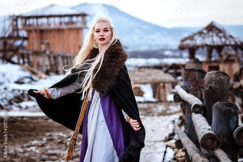 Plakát  Beautiful young woman holding a viking with blond hair