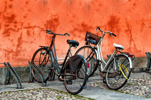 Fotobehang Fiets Two classic retro bicycles on the street. Red wall background with copy space