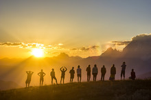 Group Of People With Hands Up Standing On Grass In Sunset Mountains
