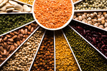 Indian Beans,Pulses,Lentils,Rice And Wheat Grain In A White Sunburst Or Sun Rays Shape Designer Container , Selective Focus.