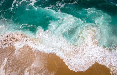 FototapetaSand beach aerial, top view of a beautiful sandy beach aerial shot with the blue waves rolling into the shore