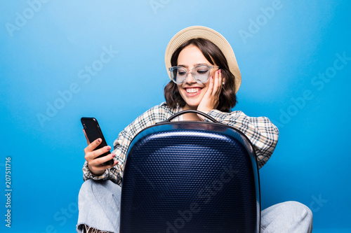 Young pretty woman in sunglasses and straw hat with a suitcase looks into the phone isolated on blue background. Flight traveling.