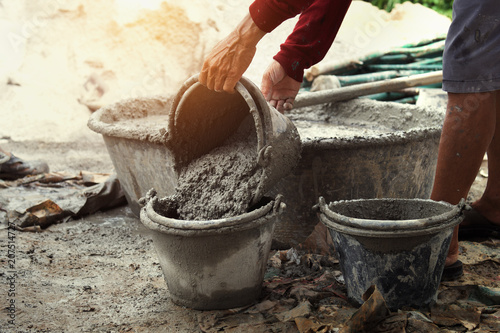 Photo  worker pouring cement mix concrete in tray