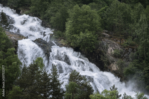 Foto op Canvas Watervallen Roaring powerful waterfall through a forest in Norway