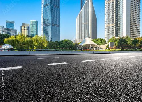 Plakat pusta asfaltowa droga z budynkiem biurowym