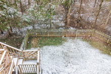 Closeup Of Empty Wooden Deck Of House With Staircase, Steps, Stairs, Trees, Forest, Lawn Grass In Backyard In Neighborhood With Snow Covered Ground During Blizzard White Storm, Snowflakes Falling