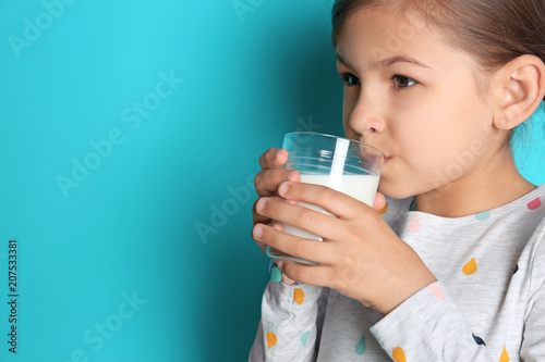 Cute little girl drinking milk on color background