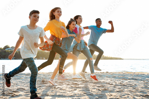 Valokuva  Group of children running on beach. Summer camp